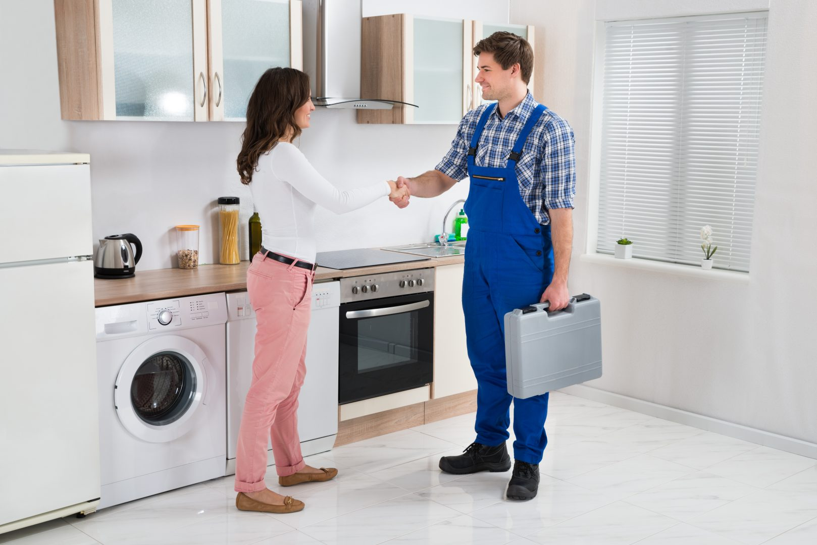 Trust Greenville Plumbing experts from Sunrise Heating & Plumbing. A plumber fixes a dishwasher, thanked by a woman.
