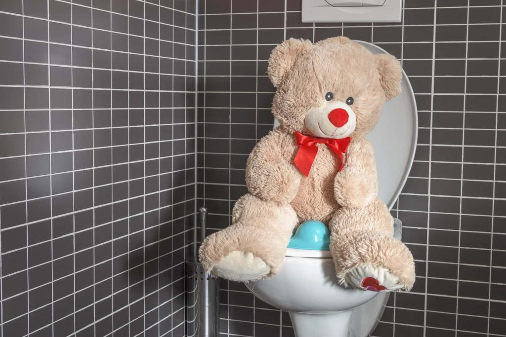 A teddy bear sits atop a clogged toilet