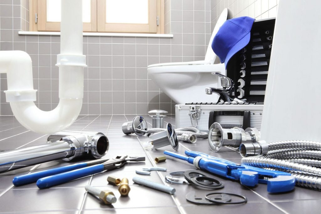 Find the right plumbing tools for the job. Various tools are laid out before pipe and toilet.