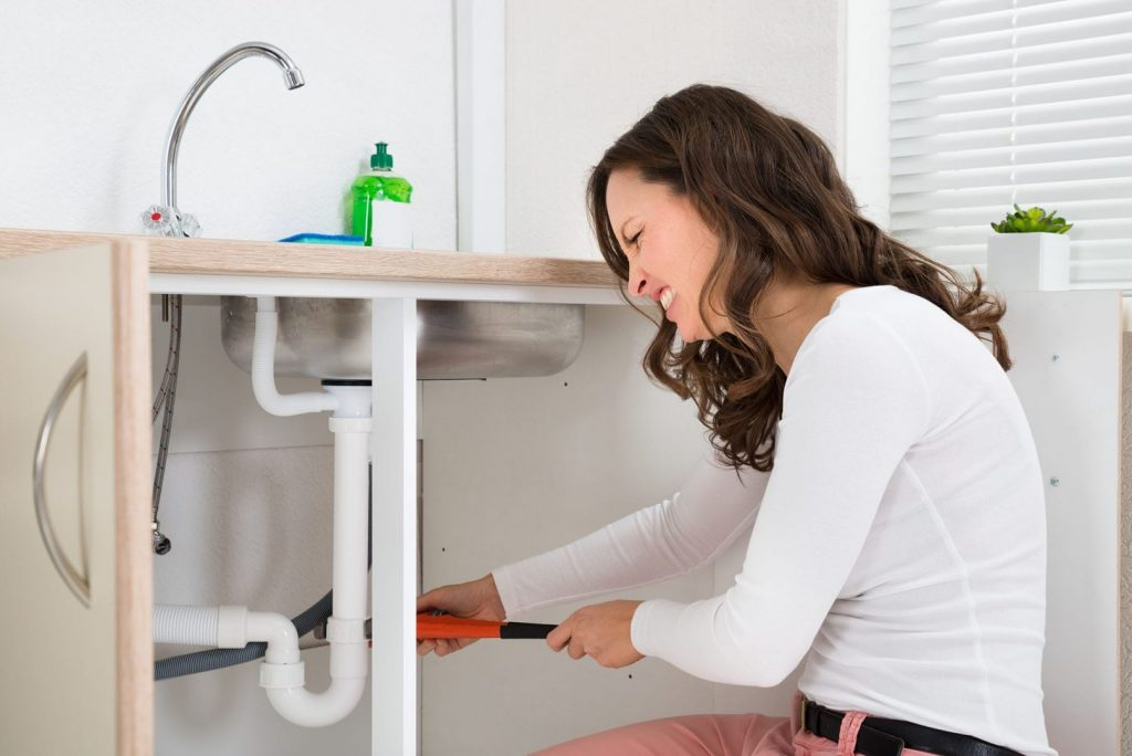 DIY Drain cleaning, a woman uses a wrench on her kitchen sink pipes.