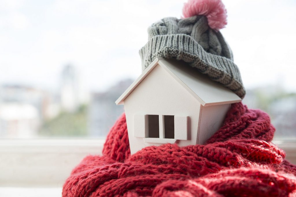 Home insulation may be the primary factor in keeping your home warm during winter. A toy wood house wrapped in a knit hat and scarf.