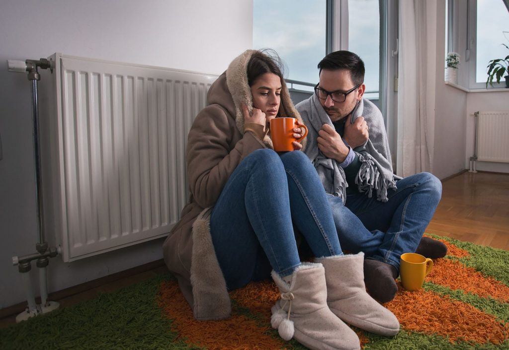 A freezing cold couple sits on the floor by their radiator. If you're too cold in your house, your furnace not turning on may be the issue.