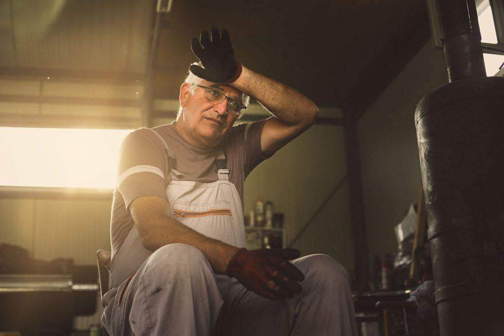 An older man fixes a furnace and sweats. Furnace noises are common, but it's when you hear them that's significant.