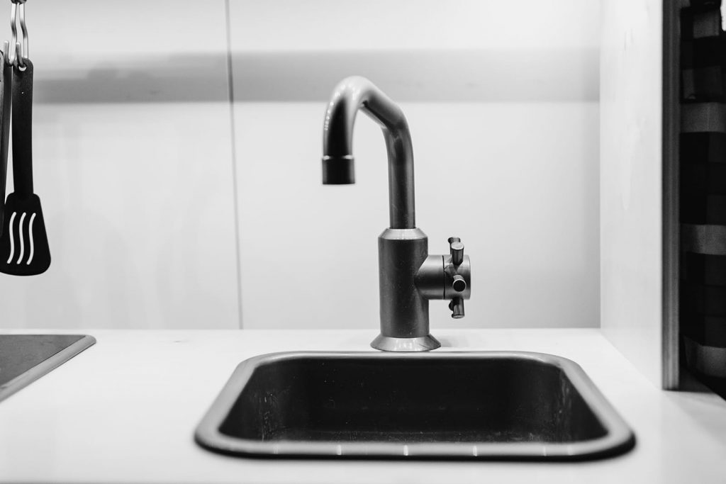 A black sink and faucet. Diagnosing plumbing issues can be as easy as identifying garbage disposal sounds.