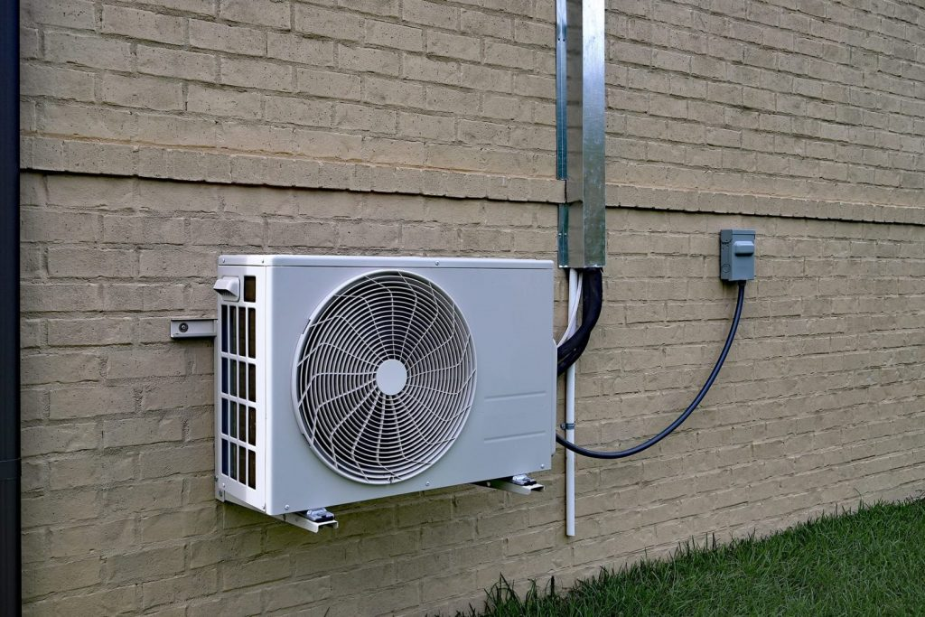 A mimi split AC system connected to a brick wall outside a home. A mini split Ac unit is a ductless hvac system.