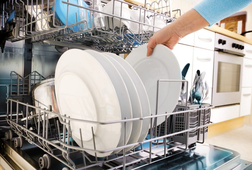 There are many tips for improving dishwasher efficiency beyond buyong a new one. A woman loading the dishwasher.