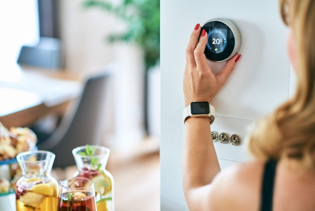 A woman changes her thermostat settings