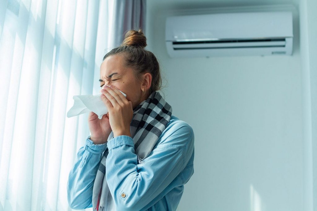 HVAC allergy solutions often go deeper than cleaning a filter. A woman sneezes in front of her indoor AC unit.