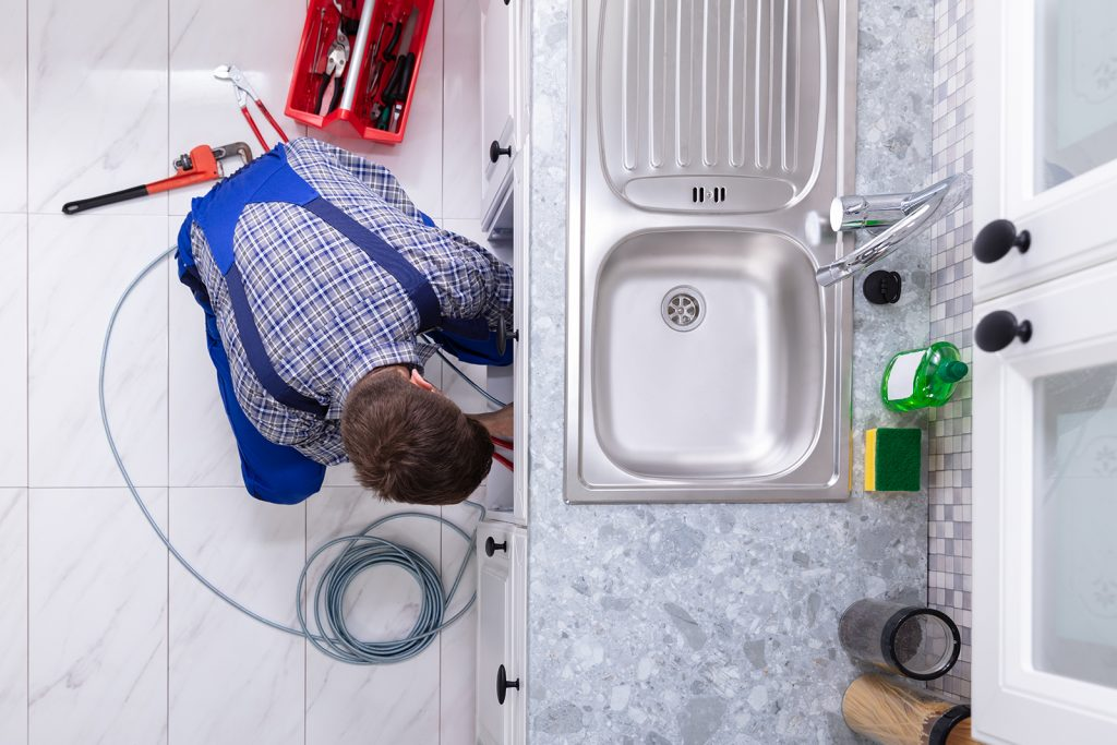 preventing drain clogs is something any homeowner can do, but calling a plumber is always a safe bet. A plumber works underneath a kitchen sink.