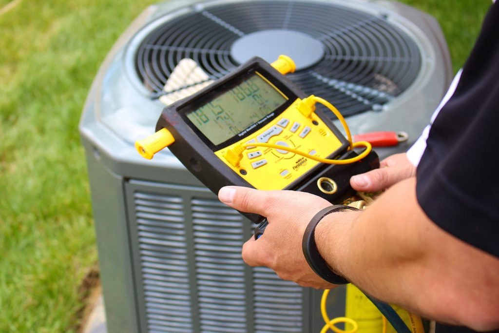 a heating technician testing an HVAC electrical output monitor next to an outdoor air conditioning unit.