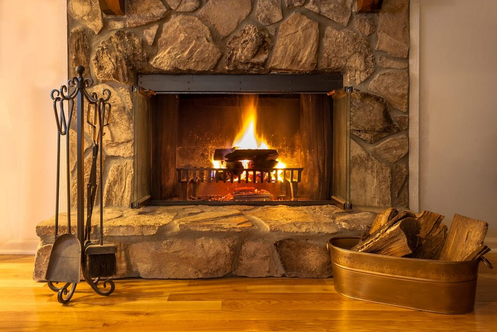 A fireplace in a stone inset. Understand the the benefits of having a fireplace with Sunrise Heating & Plumbing.