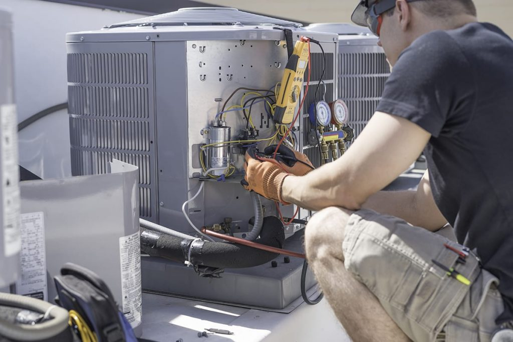 Regular HVAC maintenance is a must for new and old systems. An HVAC technician works on a rooftop air conditioner unit.