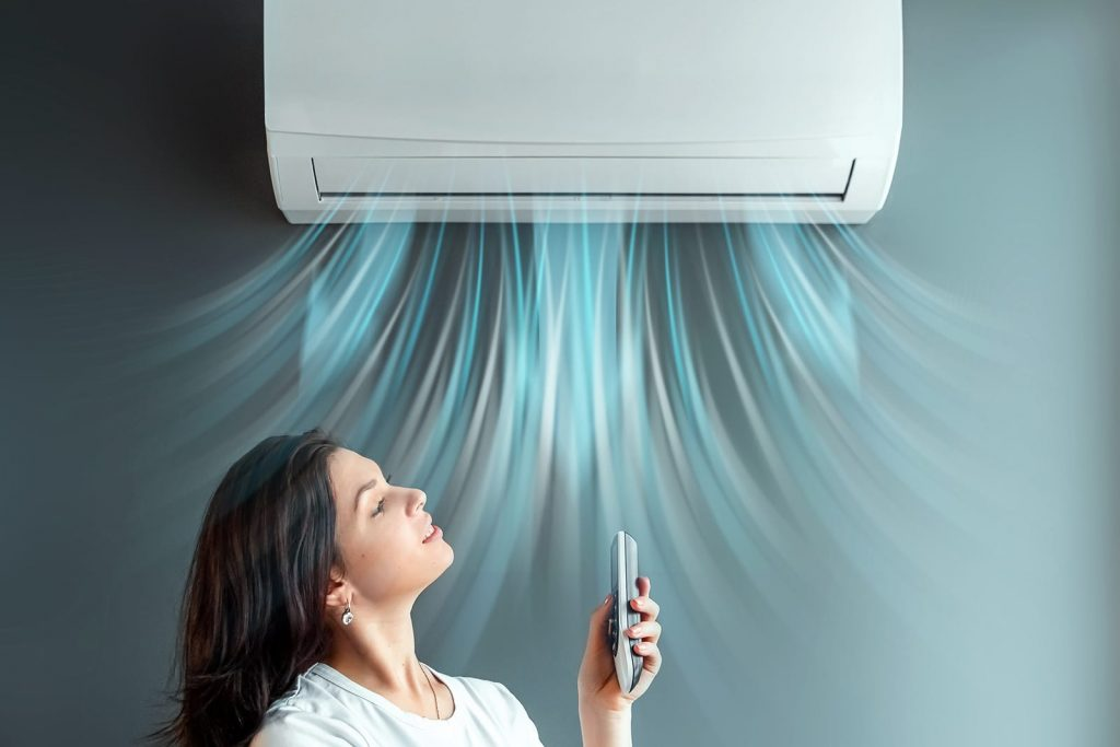 Air conditioner energy efficiency is key when you need it to run higher during a hot summer. A wall-mounted AC unit on full blast, cooling a young woman below.